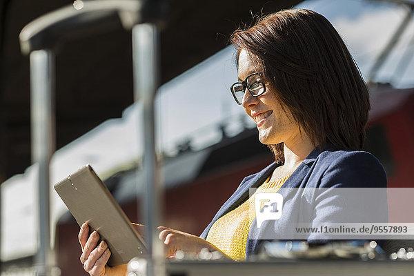 Lächelnde junge Frau mit digitalem Tablett
