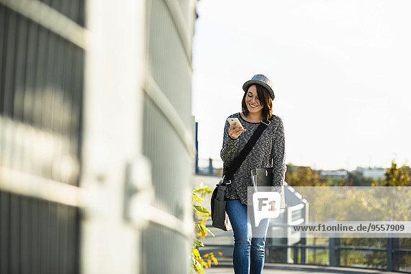 Lächelnde junge Frau mit Mappe  Tasche und Handy