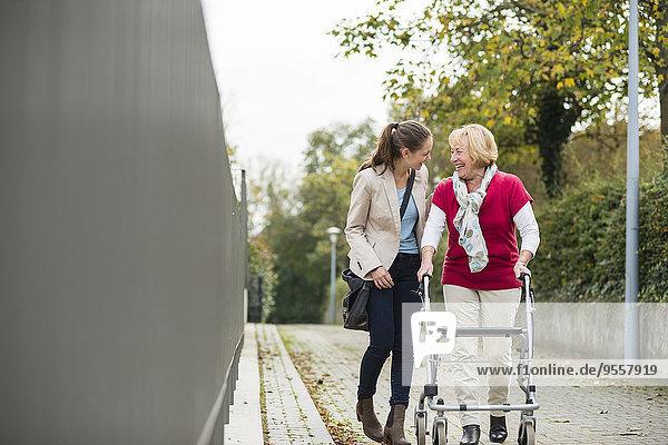 Erwachsene Enkelin  die ihrer Großmutter beim Gehen mit dem Rollator hilft.