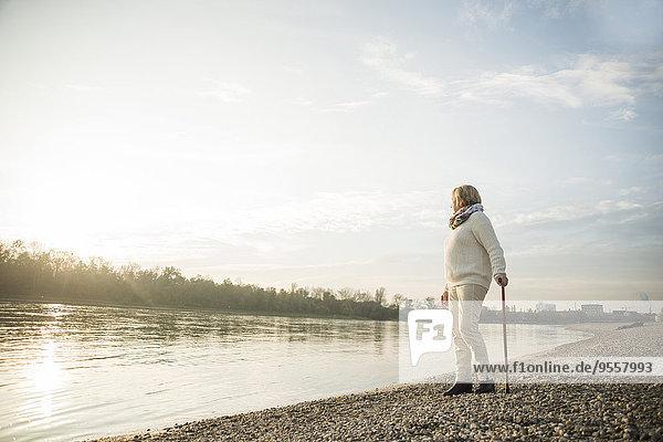 Senior woman with walking stick standing at waterside watching sunset