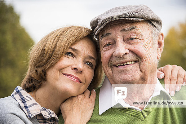 Zuversichtlicher Senior mit Tochter im Freien