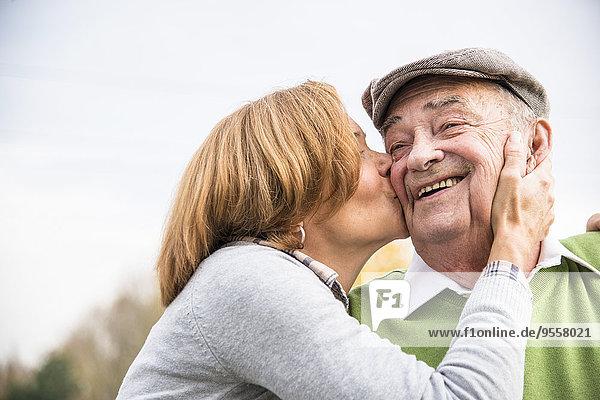 Erwachsene Tochter küsst Vaters Wange