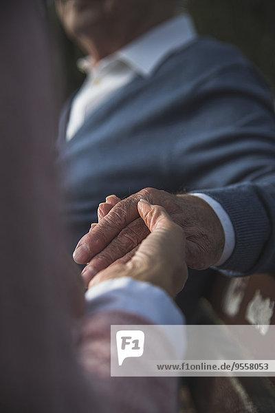 Daughter holding hand of senior man