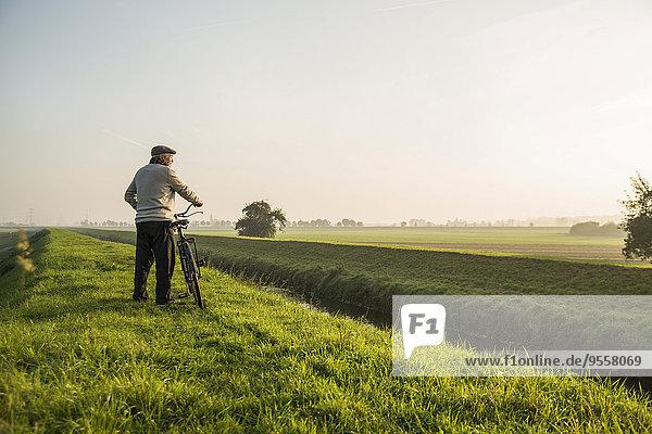 Älterer Mann in ländlicher Landschaft schiebt Fahrrad
