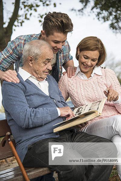 Senior Mann mit Enkel und Tochter beim Betrachten des Fotoalbums