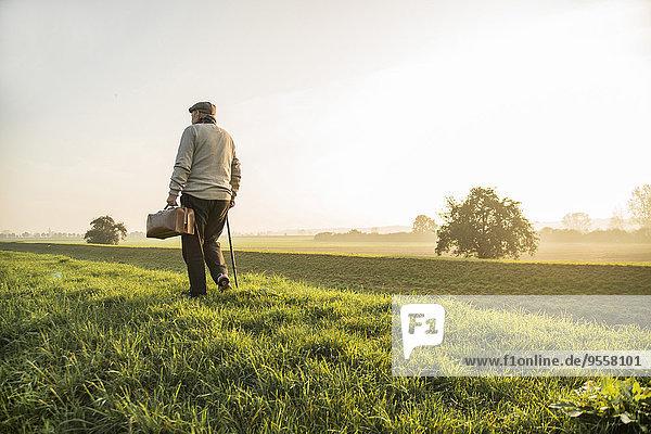 Älterer Mann mit Tasche beim Wandern in ländlicher Landschaft