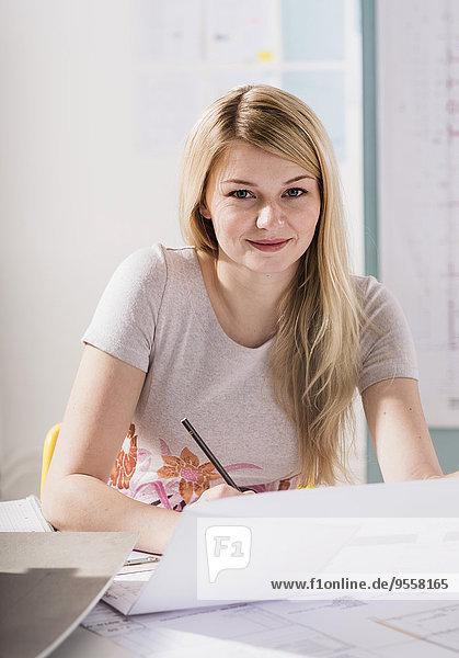 Porträt einer blonden jungen Frau am Schreibtisch