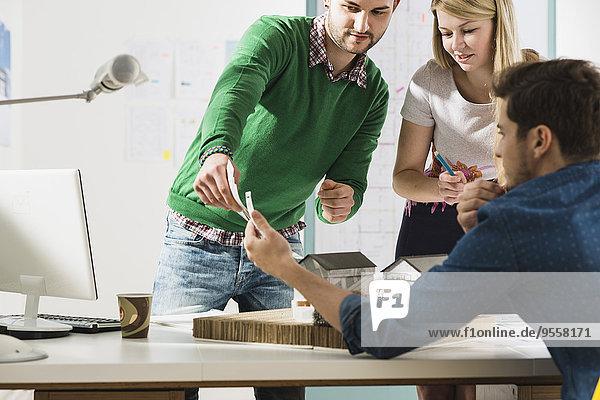 Drei junge Architekten im Büro bei der Diskussion