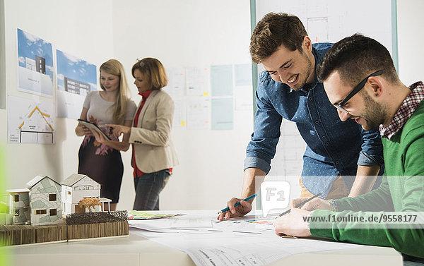 Junge Architekten im Büro mit Blick auf den Bauplan