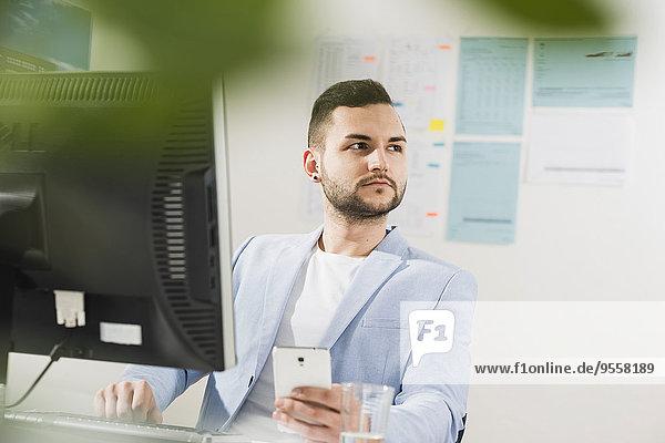 Jungunternehmer im Büro mit Computer und Handy