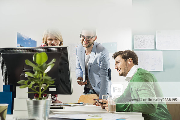 Drei junge Leute im Büro schauen auf den Computerbildschirm