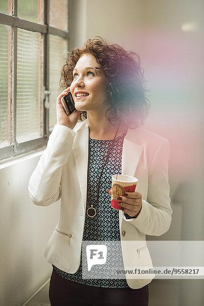 Junge Geschäftsfrau am Handy schaut aus dem Fenster