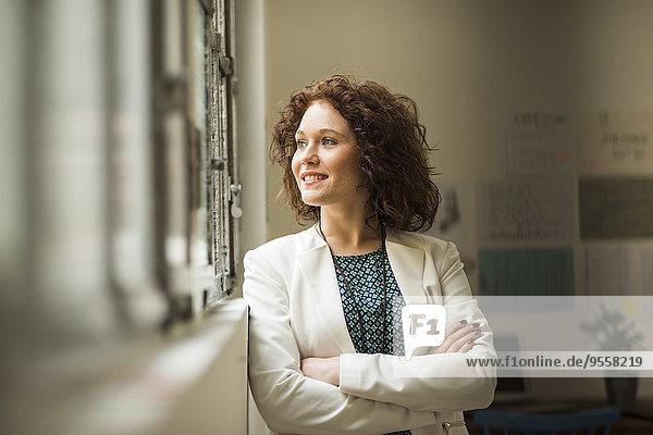 Lächelnde junge Geschäftsfrau schaut aus dem Fenster