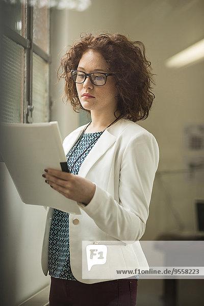 Junge Geschäftsfrau liest Dokument