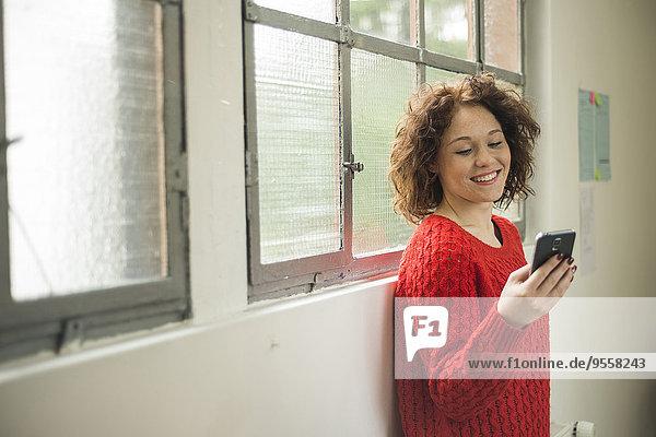Lächelnde junge Frau mit Handy am Fenster