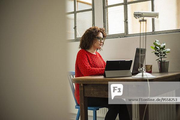 Junge Frau mit Laptop am Tisch