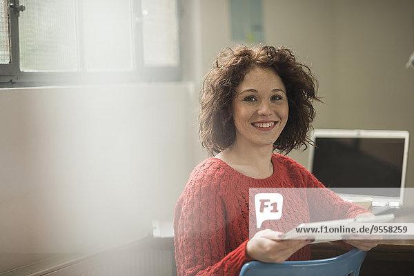 Porträt einer lächelnden brünetten jungen Frau mit digitalem Tablett