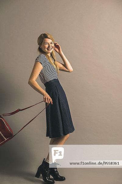 Porträt einer blonden jungen Frau mit Tasche