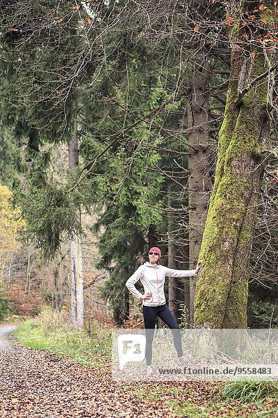 Joggerin auf Baumstamm im Wald lehnend