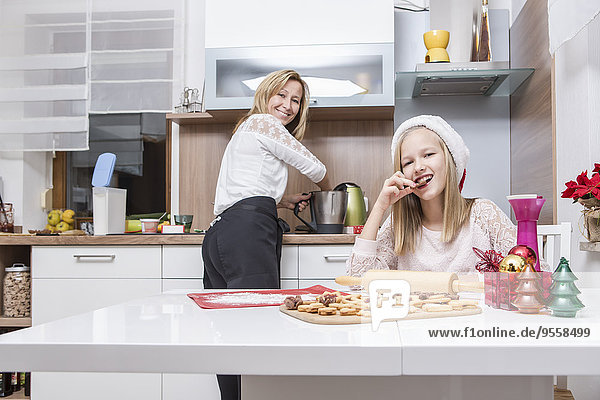 Mother and daughter baking Christmas cookies at home