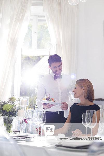 Kellner serviert Abendessen für die Frau in einem eleganten Restaurant.