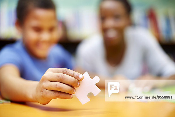 Junge Frau und Junge beim Puzzle in der Bibliothek