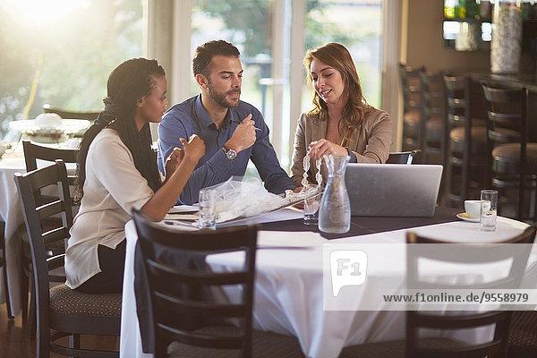 Geschäftstreffen von drei Personen in einem Restaurant