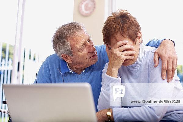Senior Mann tröstet weinende Frau am Laptop