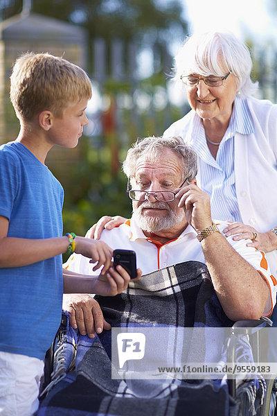 Großmutter und Enkel erklären Großvater im Rollstuhl Handy