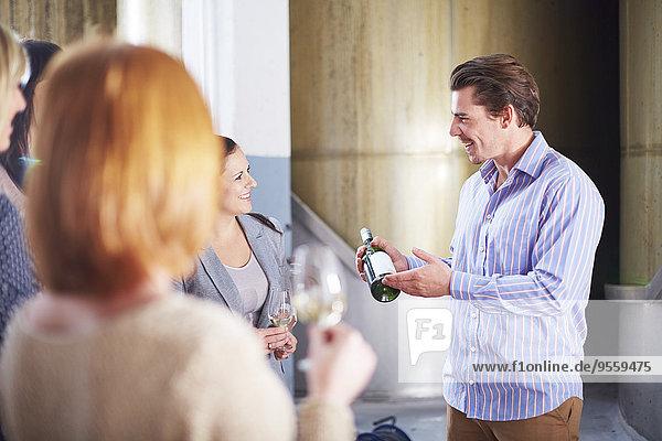 Mann präsentiert Flasche Wein in der Werkstatt