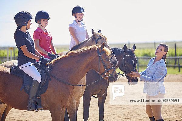 Kutsche und Mädchen auf Pferden auf dem Reitplatz