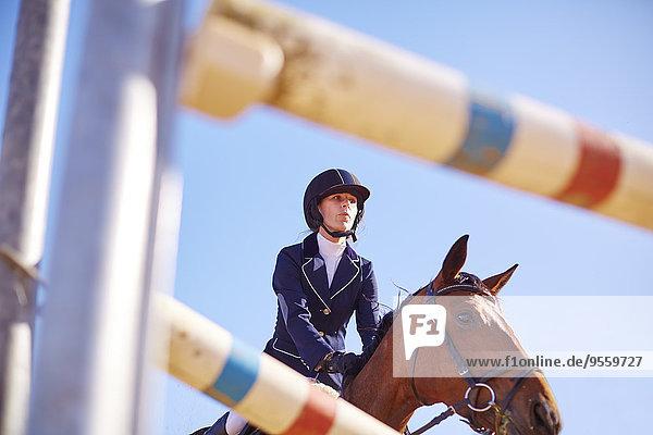 Junge Frau auf Pferd nähert sich Hindernis auf Kurs