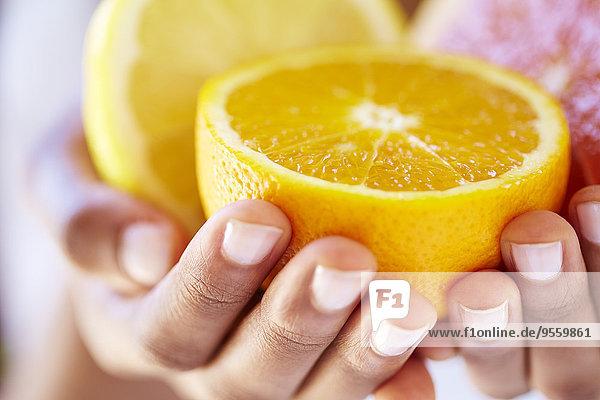 Frauenhände mit Orangen- und Grapefruithälften Frauenhände mit Orangen- und Grapefruithälften