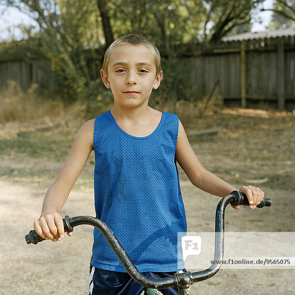 Ein Junge sitzt auf einem Fahrrad.