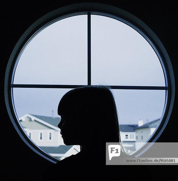 Ein Kind im Profil in einem runden Fenster