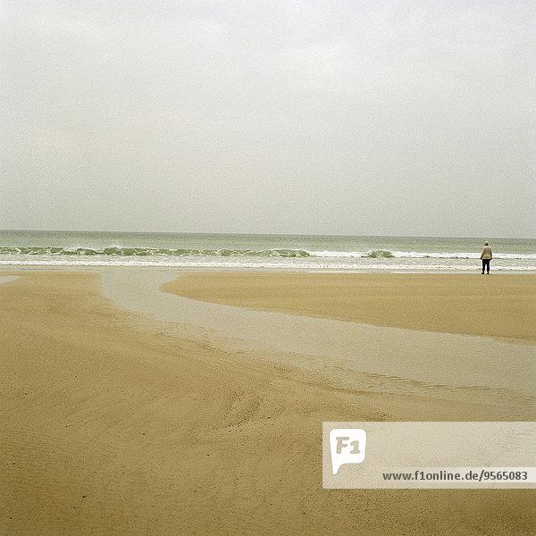 Eine Person  die am Strand steht.
