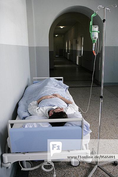Ein Mann  der in einem Krankenhausbett liegt.