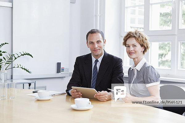 Ein Geschäftsmann und eine Geschäftsfrau  die ein digitales Tablett in einer Besprechung verwenden.