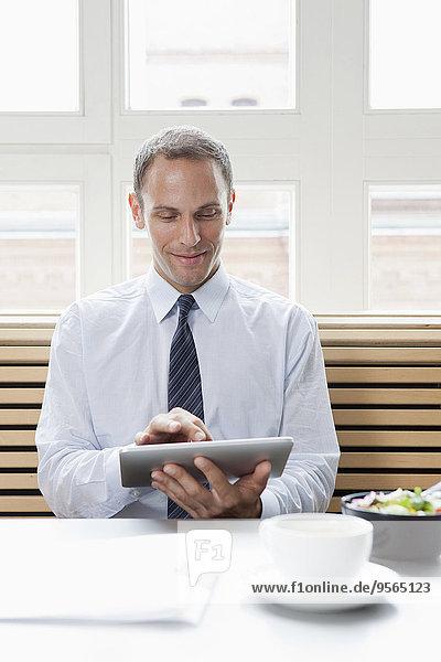 Ein Geschäftsmann  der in seiner Mittagspause ein digitales Tablett benutzt.