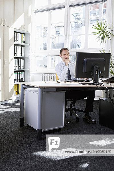 Ein Geschäftsmann  der in seinem Büro arbeitet.