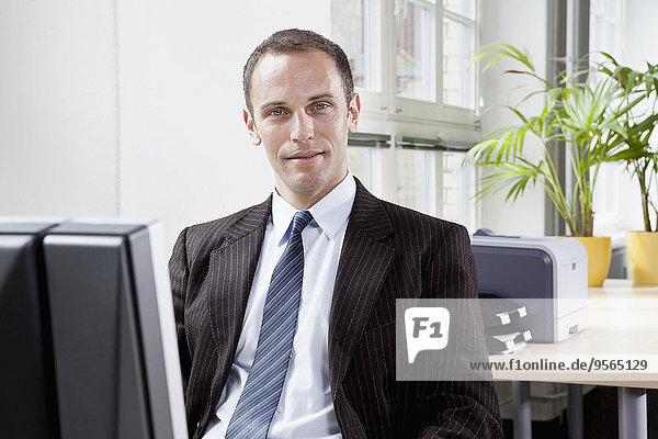 Ein Geschäftsmann  der an einem Schreibtisch in seinem Büro sitzt.