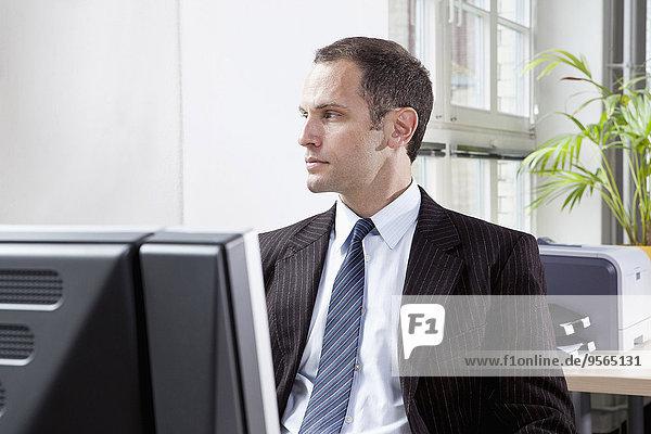 Ein Geschäftsmann sitzt an seinem Schreibtisch und schaut nachdenklich weg.