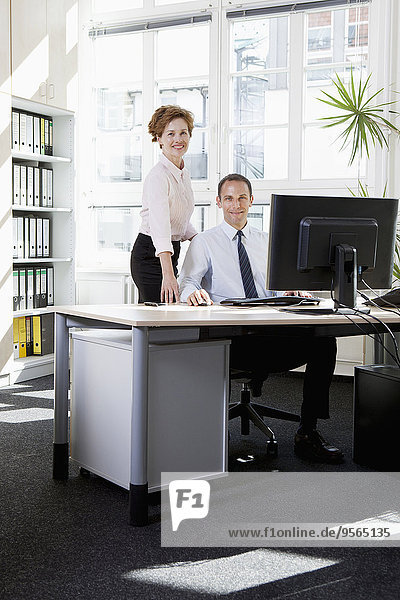 Eine Geschäftsfrau  die einem Geschäftsmann hilft  der an einem Computer sitzt.