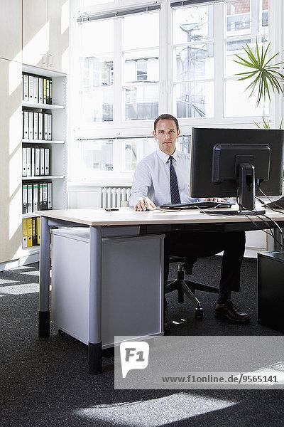Ein Geschäftsmann  der an einem Computer in einem Büro arbeitet.