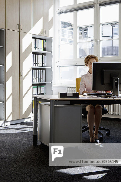 Eine Geschäftsfrau  die an einem Desktop-PC in einem Büro arbeitet.