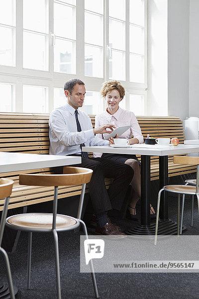 Geschäftskollegen  die ein digitales Tablett während eines Geschäftsessens verwenden