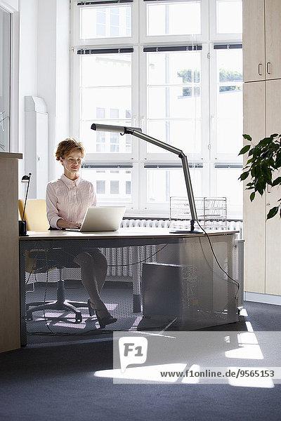 Eine Geschäftsfrau  die einen Laptop in einem Büro benutzt.