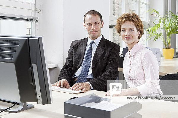 Ein Geschäftsmann und eine Geschäftsfrau  die zusammen an einem Computer arbeiten.