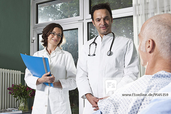Zwei Ärzte neben einem männlichen Patienten auf einer Krankenstation
