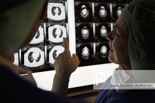Ein Arzt  der Röntgenstrahlen auf einem Leuchtkasten betrachtet.
